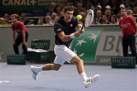Novak Djokovic of Serbia hits a return to Roger Federer of Switzerland in their semi-final match at the Paris Masters men's singles tennis tournament at the Palais Omnisports of Bercy in Paris, November 2, 2013. REUTERS/Gonzalo Fuentes