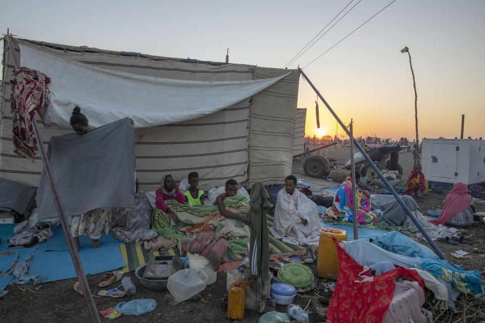 Tigray refugees who fled the conflict in the Ethiopia's Tigray sit up after waking up in the early morning at Hamdeyat Transition Center near the Sudan-Ethiopia border, eastern Sudan, Thursday, Dec. 3, 2020. Ethiopian forces on Thursday blocked people from the country's embattled Tigray region from crossing into Sudan at the busiest crossing point for refugees, Sudanese forces said.(AP Photo/Nariman El-Mofty)