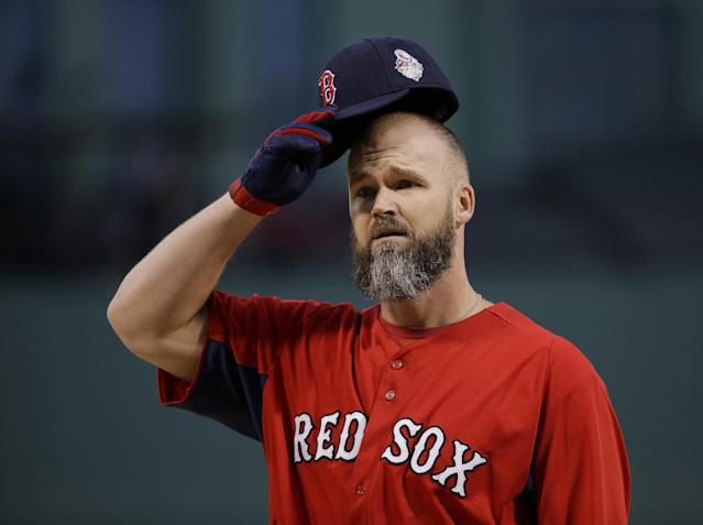 Boston Red Sox's David Ross puts on his cap during practice before Game 1 of baseball's World Series against the St. Louis Cardinals Wednesday, Oct. 23, 2013, in Boston. (AP Photo/Matt Slocum)