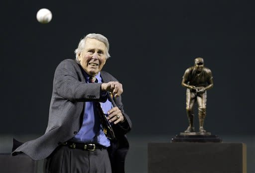Former Baltimore Orioles third baseman Brooks Robinson throws out the first pitch in front of a replica of a statue of him that was unveiled before a baseball game between the Orioles and the Boston Red Sox in Baltimore, Saturday, Sept. 29, 2012. (AP Photo/Patrick Semansky)