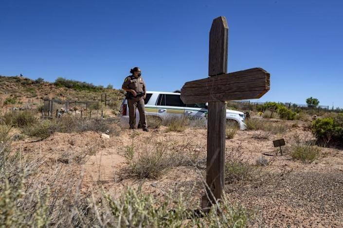 TUBA CITY, AZ - MAY 22: Navajo Nation police officer Carolyn Tallsalt looks out at dried sagebrush where her uncle George Billy was buried in April at the Tuba City Community Cemetery on Friday, May 22, 2020 in Tuba City, AZ. Lockdown curfews are being enforced over the weekends in an effort to slow the coronavirus' spread. (Brian van der Brug / Los Angeles Times)