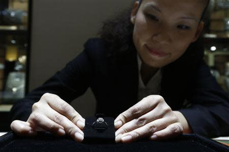 A sales assistant displays a diamond ring at a Tiffany store in Shanghai, September 16, 2013. REUTERS/Aly Song