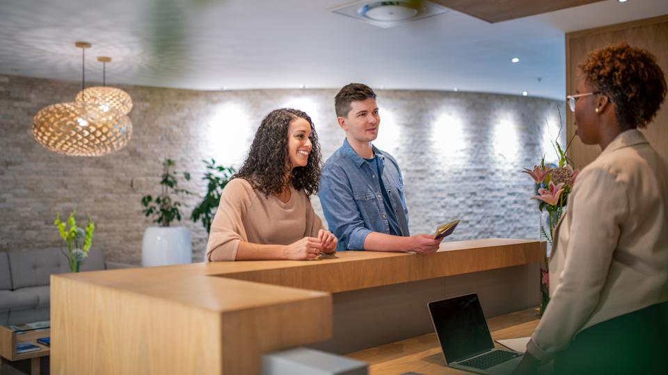 Mid adult couple discussing with female receptionist.