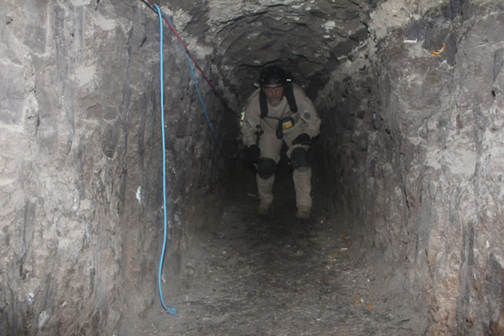 An agent from the San Diego Tunnel Task Force walks through part of the passageway of a tunnel found under the U.S.-Mexico border, in San Diego, November 26, 2010.   U.S. border agents said on Friday they had found a half-mile-long tunnel under the U.S.-Mexico border and seized a significant amount of marijuana at the San Diego area warehouse where it ends.    REUTERS/U.S. Immigration and Customs Enforcement (ICE)/Handout     (UNITED STATES - Tags: CRIME LAW POLITICS SOCIETY) FOR EDITORIAL USE ONLY. NOT FOR SALE FOR MARKETING OR ADVERTISING CAMPAIGNS. THIS IMAGE HAS BEEN SUPPLIED BY A THIRD PARTY. IT IS DISTRIBUTED, EXACTLY AS RECEIVED BY REUTERS, AS A SERVICE TO CLIENTS
