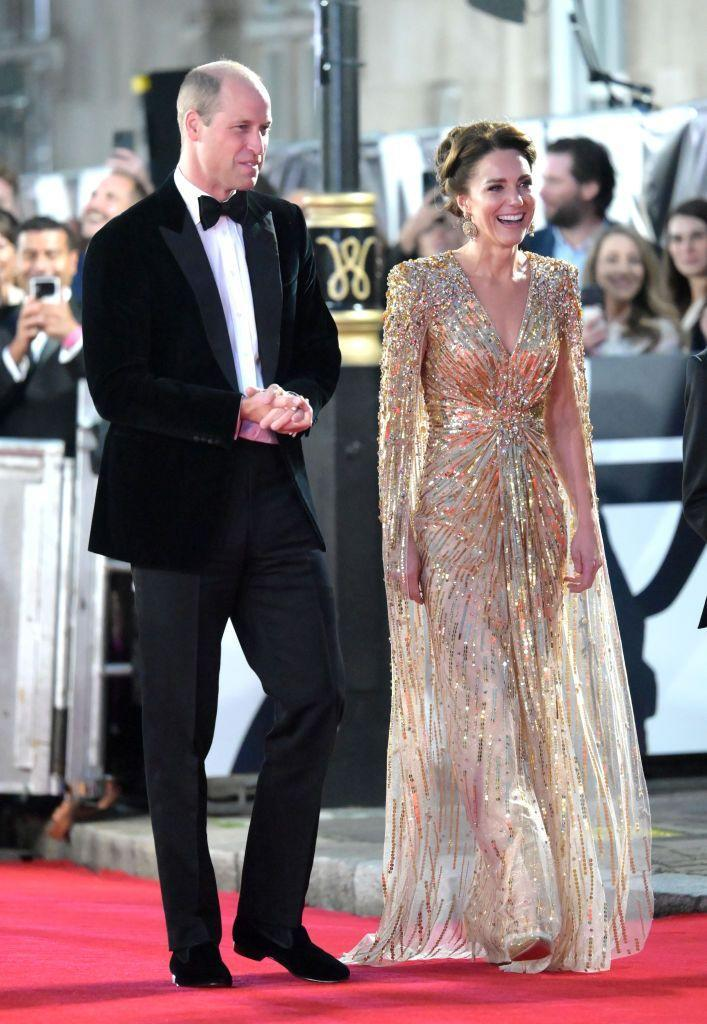 """<p>Kate looked on theme for the London premiere of No Time to Die, the latest James Bond feature. The Duchess sparkled in an <a href=""""https://www.townandcountrymag.com/society/tradition/a37710183/kate-middleton-james-bond-premiere-gold-dress-photos/"""" rel=""""nofollow noopener"""" target=""""_blank"""" data-ylk=""""slk:embellished, gold cape dress"""" class=""""link rapid-noclick-resp"""">embellished, gold cape dress</a> from one of her beloved designers, Jenny Packham. </p>"""