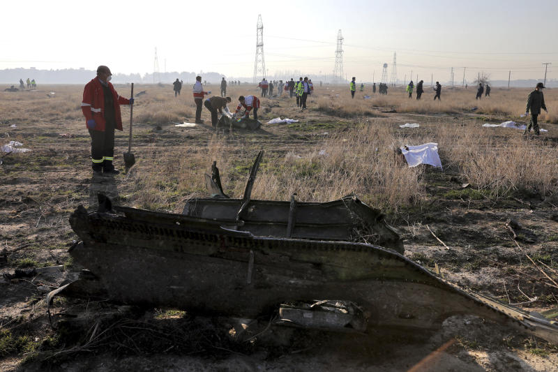 In this Wednesday, Jan. 8, 2020 photo, rescue workers search the scene where a Ukrainian plane crashed in Shahedshahr, southwest of the capital Tehran, Iran. Iran on Friday denied Western allegations that one of its own missiles downed a Ukrainian jetliner that crashed outside Tehran, and called on the U.S. and Canada to share any information they have on the crash, which killed all 176 people on board. (AP Photo/Ebrahim Noroozi)