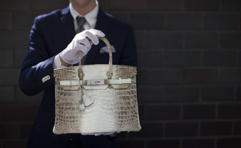 An employee holds an Hermes diamond and Himalayan Nilo Crocodile Birkin handbag at Heritage Auctions offices in Beverly Hills, CA on Sept. 22, 2014. The handbag has 242 diamonds with a total of 9.84 carats. (Mario Anzuoni / Reuters)