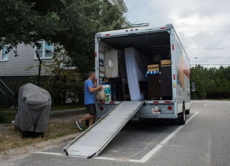 Greg Cook and his wife rush to clear out their things before the arrival of Hurricane Florence to Wrightsville Beach, North Carolina