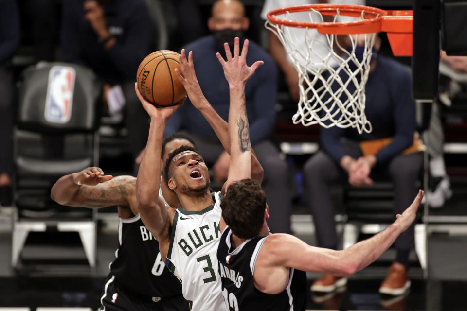 Milwaukee Bucks forward Giannis Antetokounmpo (34), center, drives to the basket against Brooklyn Nets forward Joe Harris during the second half of an NBA basketball game Monday, Jan. 18, 2021, in New York. (AP Photo/Adam Hunger)