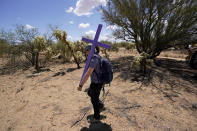 Alyssa Quintanilla, part of the Tucson Samaritans volunteer group, carries a cross Tuesday, May 18, 2021, to be installed at the site of the migrant who died in the desert some time ago, in the desert near Three Points, Ariz. Protecting migrants and honoring the humanity of those who died on the perilous trail is a kind of religion in southern Arizona where spiritual leaders four decades ago founded the Sanctuary Movement, a campaign to shelter Central Americans fleeing civil war, and scores of volunteers carry on their legacy today. (AP Photo/Ross D. Franklin)