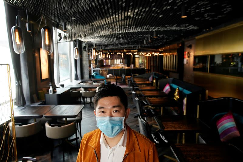 Founder and CEO of seul&SEUL restaurant Hu wears a mask and poses for pictures in downtown Shanghai