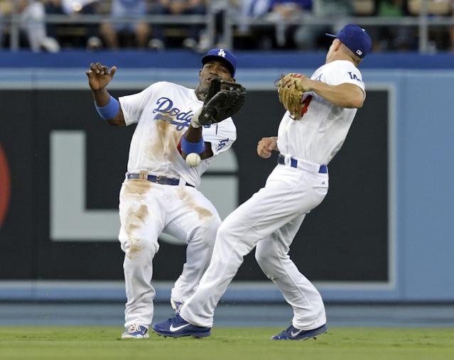 Los Angeles Dodgers center fielder Yasiel Puig, left, and second baseman Mark Ellis let a fly ball by San Francisco Giants' Brandon Belt drop during the second inning of a baseball game in Los Angeles on Saturday, Sept. 14, 2013. (AP Photo/Reed Saxon)