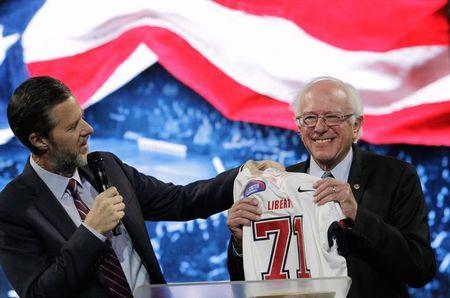 U.S. Democratic presidential candidate Sen. Bernie Sanders (I-VT) receives a football jersey from Jerry Falwell Jr., president of Liberty University after addressing students in Lynchburg