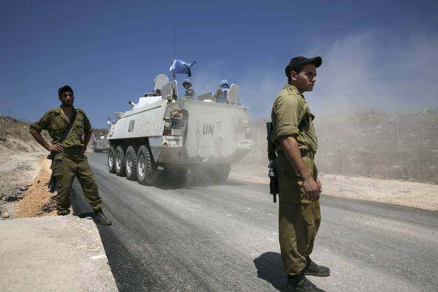 Members of the United Nations Disengagement Observer Force (UNDOF) ride armoured personnel carriers (APCs) past Israel soldiers in the Israeli-occupied Golan Heights, before crossing into Syria August 31, 2014. The head of the Fijian army said on Sunday negotiations for the release of 44 soldiers seized by an al Qaeda-linked group on the Syrian side of the Golan Heights were being pursued but he worried there had been no word on where his men are being held. REUTERS/Baz Ratner (CIVIL UNREST POLITICS CONFLICT TPX IMAGES OF THE DAY)