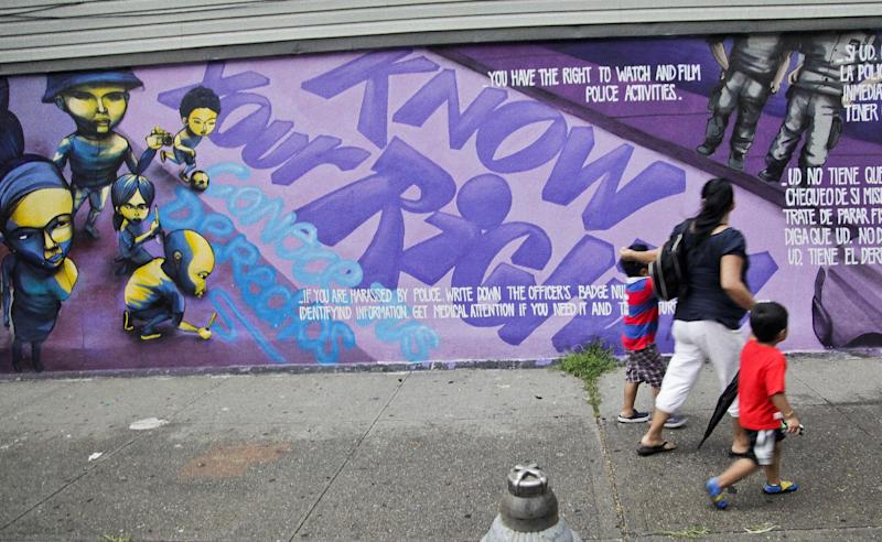 """FILE - In this July 18, 2012 photo, A woman and children walk past a street mural depicting individual rights during a """"Stop and Frisk"""" on in New York. The New York City Council Public Safety Committee will hear proposals to impose new requirements for police """"stop-and-frisk"""" encounters, a strategy of detaining and sometimes searching anyone officers deem suspicious, but critics argue the practice is discriminatory and unfairly targets minorities. (AP Photo/Bebeto Matthews, File)"""