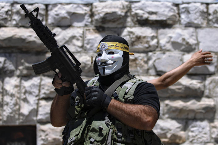 A masked Palestinian protester shoots in the air following the funeral of Mohammed al-Alami, 12, in the village of Beit Ummar, near the West Bank city of Hebron, Thursday, July 29, 2021. Villagers say the boy was fatally shot by Israeli troops while traveling with his father in a car. The Israeli military has launched an investigation into the shooting. (AP Photo/Majdi Mohammed)