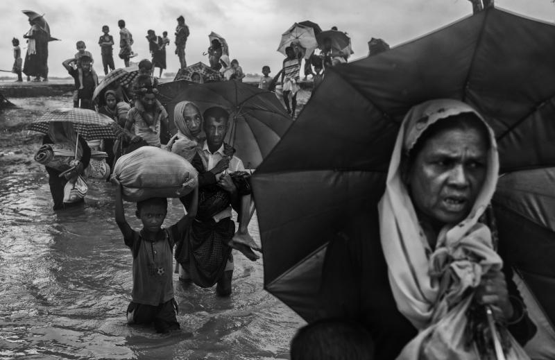 Rohingya refugees carry their belongings as they walk through water on the Bangladesh side of the Naf River after fleeing their village in Myanmar. (Kevin Frayer via Getty Images)