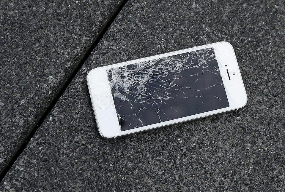 FILE - This Aug. 26, 2015, file photo shows an Apple iPhone with a cracked screen after a drop test at the offices of SquareTrade in San Francisco. In a new service offered by Dish, technicians will start making house calls to replace iPhone batteries and broken screens. Dish plans to extend the service to Android phones later. The new program represents Dish's latest effort to diversify its business as it faces a decline in TV subscribers. (AP Photo/Ben Margot, File)
