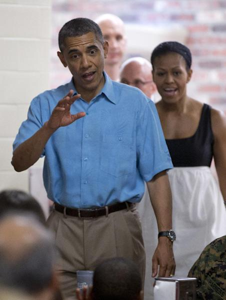 President Barack Obama and first lady Michelle Obama arrive to visit with members of the military and their families in Anderson Hall at Marine Corp Base Hawaii, Tuesday, Dec. 25, 2012, in Kaneohe Bay, Hawaii. The first family is in Hawaii for a family holiday vacation. (AP Photo/Carolyn Kaster)