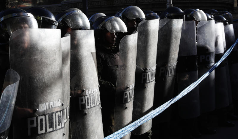 Police stand guard outside the top electoral court where protesters who are against the reelection of President Evo Morales wait for the final results of last weekend's presidential election in La Paz, Bolivia, Wednesday, Oct. 23, 2019. Morales said Wednesday his opponents are trying to stage a coup against him as protests grow over a disputed election he claims he won outright, while a nearly finished vote count had him teetering on the threshold between getting the win or having to go to a runoff. (AP Photo/Juan Karita)
