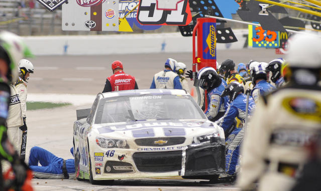 The crew for Jimmie Johnson (48) works on his car in the pits during the NASCAR Sprint Cup series auto race at Texas Motor Speedway, Monday, April 7, 2014, in Fort Worth, Texas. (AP Photo/Ralph Lauer)