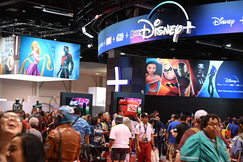 "Attendees visit the Disney+ streaming service booth at the D23 Expo, billed as the ""largest Disney fan event in the world,"" on August 23, 2019 at the Anaheim Convention Center in Anaheim, California. - Disney Plus will launch on November 12 and will compete with out streaming services such as Netflix, Amazon, HBO Now and soon Apple TV Plus. (Photo by Robyn Beck / AFP) (Photo credit should read ROBYN BECK/AFP/Getty Images)"