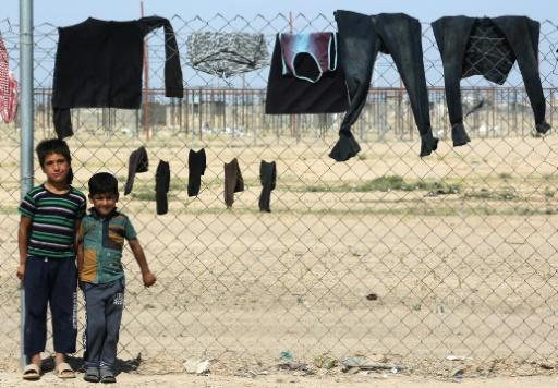 """Displaced Iraqi children stand next to a washing line in """"Camp Seven"""" near al-Khalidiyeh in Iraq's western Anbar province on April 24, 2018"""