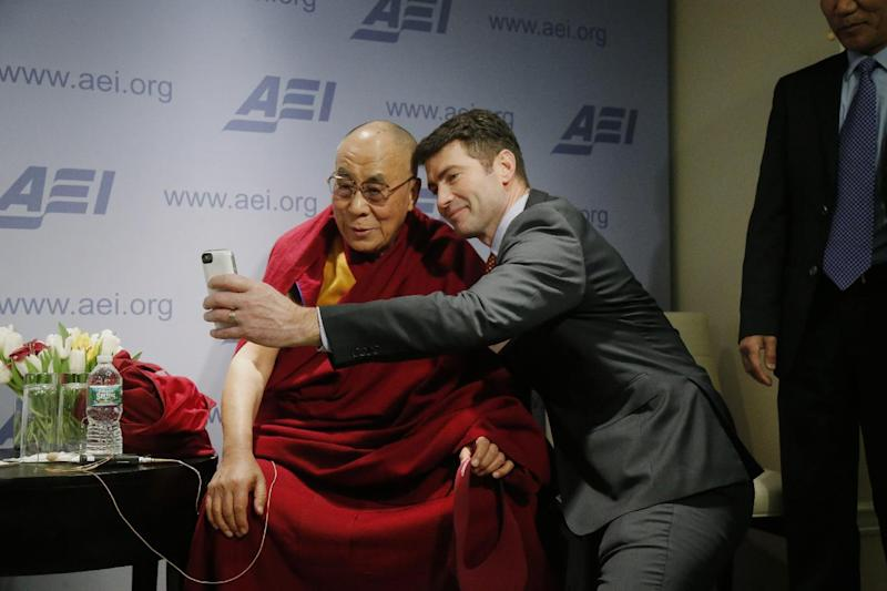 """Tibetan spiritual leader the Dalai Lama poses for a """"selfie"""" with blogger and activist Alek Boyd during a break between panel discussions at an event entitled: """"Happiness, Free Enterprise, and Human Flourishing"""" Thursday, Feb. 20, 2014, at the American Enterprise Institute in Washington. (AP Photo/Charles Dharapak)"""