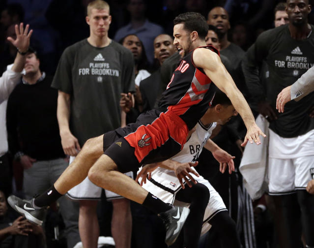 Toronto Raptors' Landry Fields, above, falls over Brooklyn Nets' Shaun Livingston, below as he chased a ball out of bounds during the second half of Game 3 of an NBA basketball first-round playoff series Friday, April 25, 2014, in New York. The Nets won t102-98. (AP Photo/Frank Franklin II)