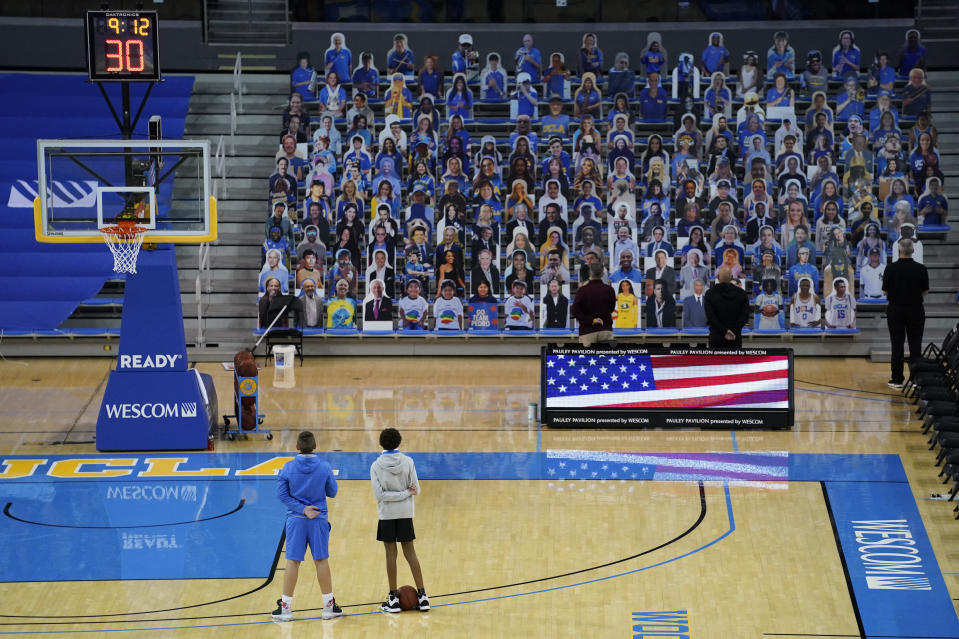Two ball boys stand on the court, facing cardboard cutouts of fans as the national anthem is played before an NCAA college basketball game between Arizona State and UCLA on Saturday, Feb. 20, 2021, in Los Angeles. (AP Photo/Ashley Landis)