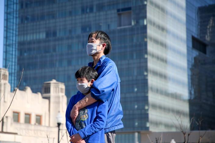 Paulo Tan holds his son, Justin, 10, both of Tulsa, while listening to a speaker during a Stop Asian Hate rally at the Center of the Universe on Friday, March 26, 2021 in Tulsa, Okla. (Ian Maule/Tulsa World via AP)