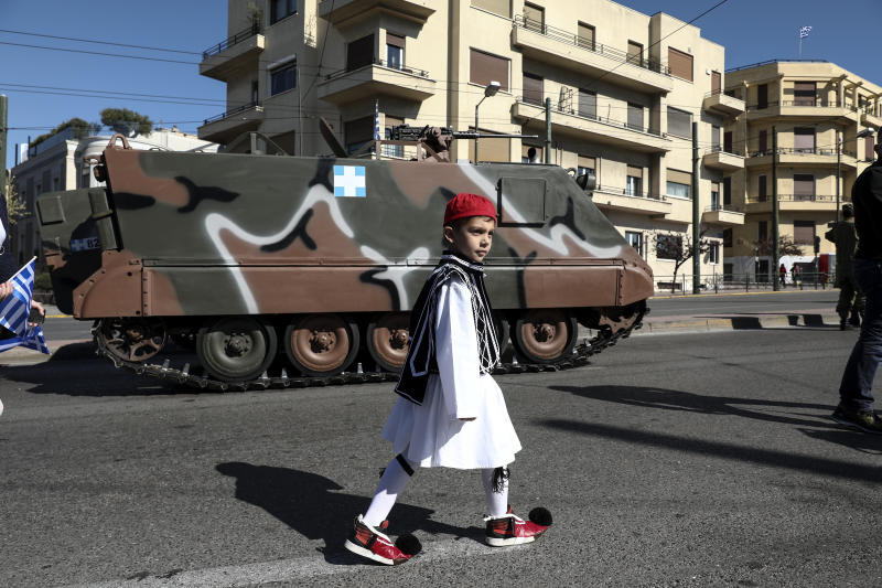 A boy dressed in traditional costume walks in front of a military vehicle ahead of a parade in Athens, on Monday March 25, 2019. The parade commemorates Greek Independence Day, which marks the start of the war of independence in 1821 against the 400-year Ottoman rule. (AP Photo/Yorgos Karahalis)