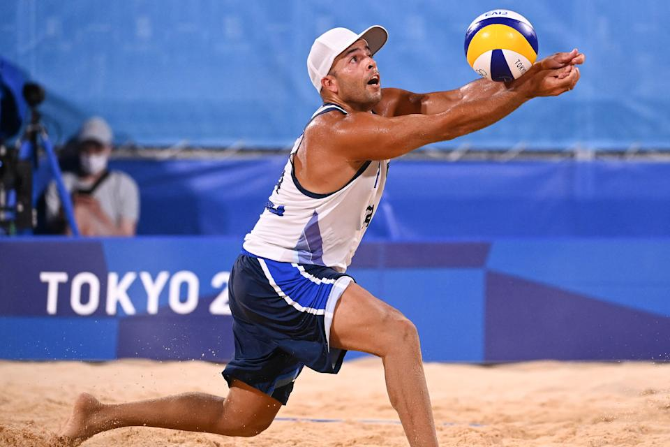 Italy's Adrian Ignacio Carambula Raurich reaches for the ball in their men's preliminary beach volleyball pool C match between the USA and Italy during the Tokyo 2020 Olympic Games at Shiokaze Park in Tokyo on July 25, 2021. (Photo by Angela WEISS / AFP) (Photo by ANGELA WEISS/AFP via Getty Images)