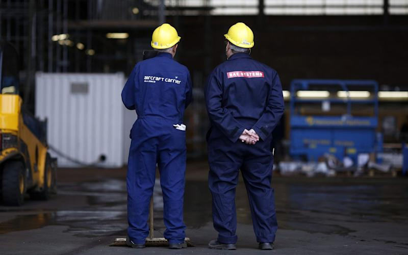 Employees take a break from working on the British Royal Navy's new HMS Prince of Wales aircraft carrier - © 2014 Bloomberg Finance LP.