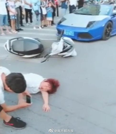 """A man records the """"collision"""" between a blogger and a Lamborghini with the blogger's mother on her scooter in Zhengzhou, Henan province. Photo: Weibo"""