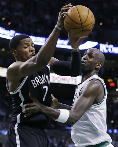 Brooklyn Nets guard Joe Johnson (7) brings down a rebound against Boston Celtics center Kevin Garnett during the second quarter of an NBA basketball game in Boston, Wednesday, April 10, 2013. (AP Photo/Elise Amendola)