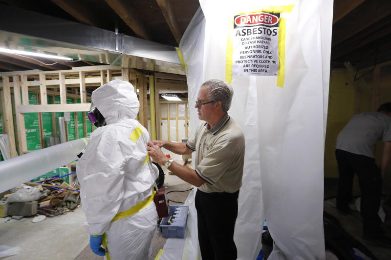 File - In this Oct. 18, 2017, file photo, George Riegel, Jr., M.D., right, owner of Asbestos Removal Technologies Inc., helps prepare a personal air monitor on job forman Megan Eberhart before asbestos abatement in Howell, Mich. Congress ordered the EPA in 2016 to gauge risks of asbestos and nine other highly toxic substances and find better ways to manage them for public safety. (AP Photo/Paul Sancya, File)