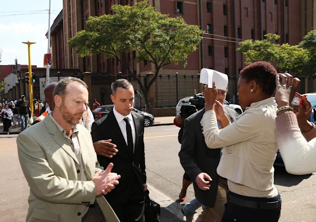 Oscar Pistorius, center, leaves as people take photos using their mobile phones after the court adjourned for the day in Pretoria, South Africa, Monday, May 5, 2014. Pistorius is charged with murder for the shooting death of his girlfriend, Reeva Steenkamp, on Valentines Day in 2013. (AP Photo/Themba Hadebe)