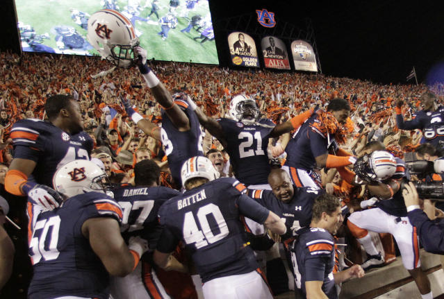 Auburn players celebrate with fans after their 43-38 win over Georgia in an NCAA college football game in Auburn, Ala., Saturday, Nov. 16, 2013. (AP Photo/Jay Sailors)