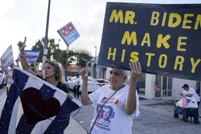 Natalie Plasencia, left, and her friend Mercedes Santana, gesture to a car parade in support of the Cuban people, Thursday, July 15, 2021, in Hialeah, Fla. The city of Hialeah has the greatest concentration of Cuban exiles in the U.S. (AP Photo/Marta Lavandier)