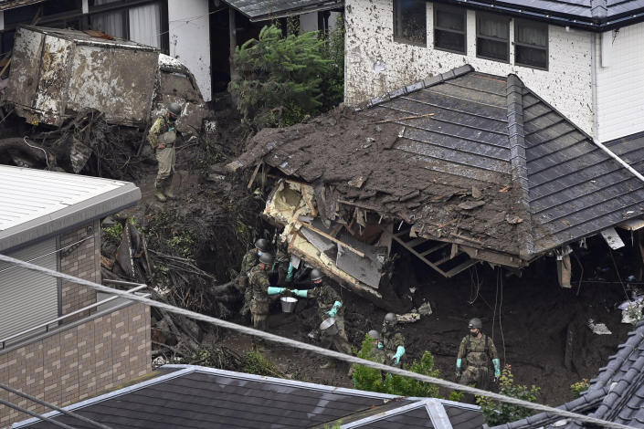 Rescuers continue a search operation for missing people at the site of a mudslide in Atami, southwest of Tokyo Wednesday, July 7, 2021. Workers are searching carefully inside homes that were destroyed and filled with mud in Saturday's disaster. (Kyodo News via AP)