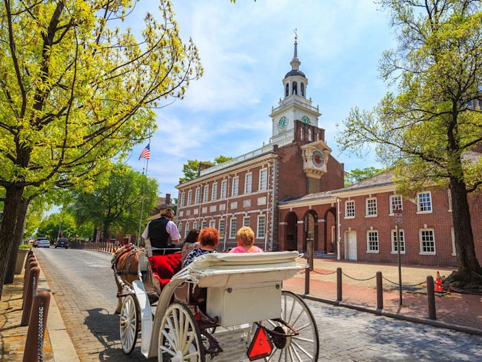 Visitors ride in a carriage past Independence Hall in Philadelphia, where the Declaration of Independence was signed.