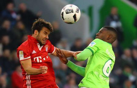 VfL Wolfsburg's Riechedly Bazoer in action with Bayern Munich's Juan Bernat