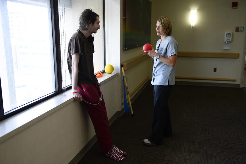 DENVER, CO - JULY 6: Physical therapist Michelle Laging(right) shows patient Dante Rana a stretch at the ACUTE Center for eating disorders Denver Health Medical Center on July 6, 2016. Dante is recovering from avoidant/restrictive food intake disorder(ARFID). (Photo by Michael Reaves/The Denver Post via Getty Images)