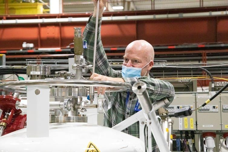 A man inserts a rod into a container of liquid hydrogen in a lab