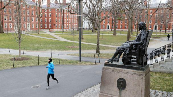 PHOTO: A runner crosses Harvard Yard on March 23, 2020, in Cambridge, Mass. Students were required to be out of their dorms no later than March 15 and finish the rest of the semester online due to the ongoing COVID-19 pandemic.. (Maddie Meyer/Getty Images, FILE)