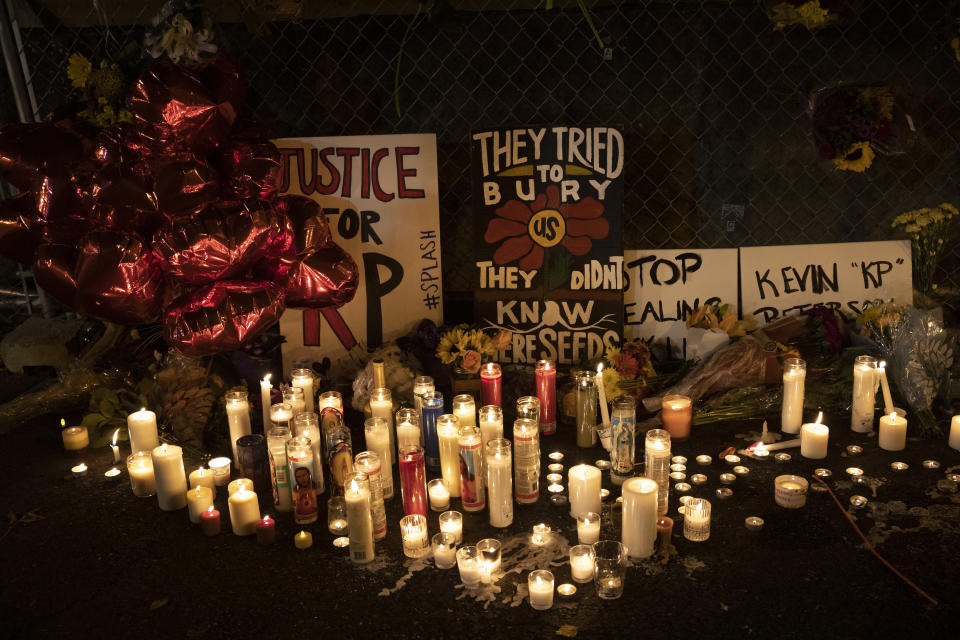 Candles and signs are seen at a memorial as people gather for Kevin Peterson Jr., who was killed in Thursday's shooting with police involved, at a candlelight vigil in Vancouver, Wash., Friday, Oct. 30, 2020. The Clark County Sheriff's office has not released any details on the Thursday evening shooting in Hazel Dell, but a man told The Oregonian/OregonLive that his 21-year-old son was fatally shot by police. (AP Photo/Paula Bronstein)