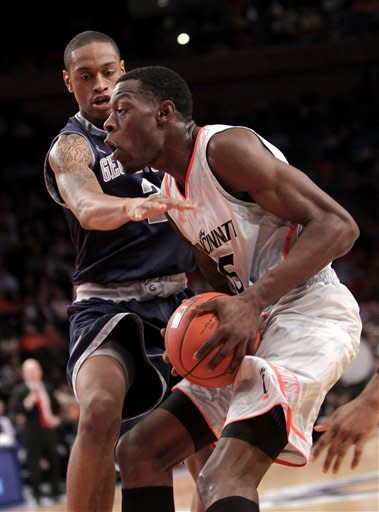 Georgetown's Greg Whittington, left, tries to stop Cincinnati's Justin Jackson during the quarterfinal round of the Big East NCAA college basketball conference tournament in New York, Thursday, March 8, 2012. (AP Photo/Seth Wenig)