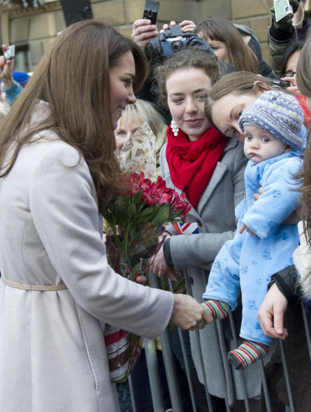 FILE - In this Wednesday Nov. 28, 2012 file photo Britain's Kate Duchess of Cambridge. left. meets with a young member of the public as she arrives at the Guildhall during a visit to Cambridge England. The Duke and Duchess of Cambridge are very pleased to announce that the Duchess of Cambridge is expecting a baby, St James's Palace officially announced Monday Dec. 3, 2012. (AP Photo/Arthur Edwards, File)