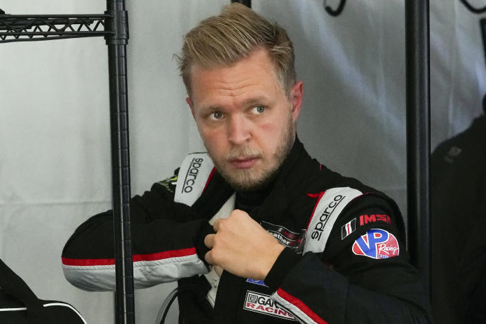 Kevin Magnussen, of Denmark, adjusts his driving suit after taking a turn on the track driving during a practice session for the Rolex 24 hour race at Daytona International Speedway, Friday, Jan. 29, 2021, in Daytona Beach, Fla. (AP Photo/John Raoux)